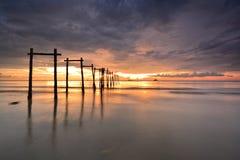 Por do sol dramático com reflexões na praia enlameada Imagem de Stock Royalty Free
