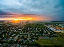Por do sol dramático da opinião aérea do zangão com névoa e nuvens acima do subúrbio em Texas central imagens de stock royalty free