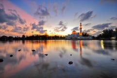 Por do sol dramático sobre a mesquita com reflexões do céu na água Imagem de Stock