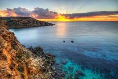 Por do sol e a água rochosa, clara da baía dourada, Malta, Europa Fotos de Stock