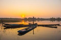 Por do sol e barcos da silhueta no lago fotos de stock