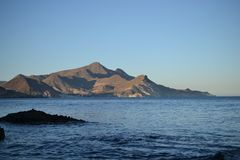 Por do sol e crepúsculo na costa do parque natural de Cabo de Gata, Almeria, Andaluzia, Espanha, área vulcanic, mar e montanhas imagens de stock