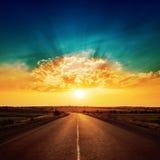 Por do sol e estrada asfaltada ao horizonte fotos de stock