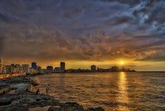 Por do sol e nuvens dramáticas sobre a skyline de Havana com os pescadores no primeiro plano imagens de stock