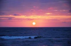 Por do sol e nuvens e mar escuros Imagem de Stock