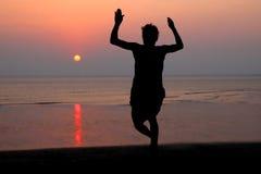 Por do sol e silhueta de um dançarino na praia Foto de Stock