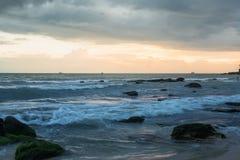Por do sol em Camboja no beira-mar Rolo das ondas do mar em areias e em rochas fotos de stock royalty free