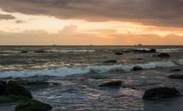 Por do sol em Camboja no beira-mar Rolo das ondas do mar em areias e em rochas foto de stock royalty free