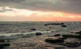 Por do sol em Camboja no beira-mar Rolo das ondas do mar em areias e em rochas imagens de stock