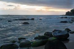 Por do sol em Camboja no beira-mar Rolo das ondas do mar em areias e em rochas fotos de stock