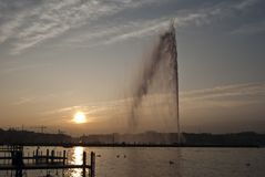 Por do sol em Genebra ` Eau de Genève do jato d foto de stock royalty free