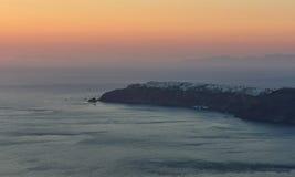 Por do sol em Santorini e na vila de Oia do fundo Fotografia de Stock Royalty Free