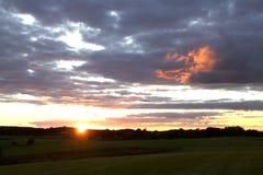 Por do sol em um campo verde fotografia de stock royalty free