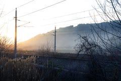 Por do sol em um cenário místico nevoento com arbustos e as trilhas pequenos do trem com linhas elétricas em styria fotos de stock