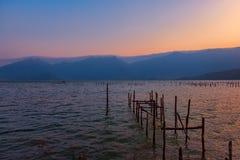 Por do sol em um lago com as sobras de um cais de madeira sob s claro fotografia de stock royalty free