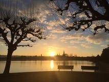 Por do sol em um lago com opinião da cidade Foto de Stock