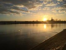 Por do sol em um lago com opinião da cidade Fotografia de Stock Royalty Free