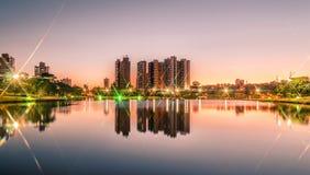 Por do sol em um lago de um parque com a cidade no fundo Fotografia de Stock Royalty Free