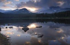 Por do sol em um lago em montanhas rochosas Imagens de Stock