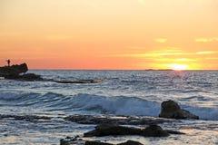 Por do sol em uma praia rochosa Imagens de Stock