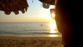 Por do sol ensolarado bonito no mar Vista através dos óculos de sol a mulher nos óculos de sol olha o por do sol no mar filme