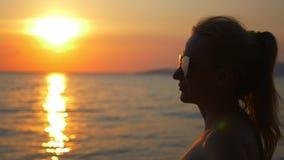Por do sol ensolarado bonito no mar Vista através dos óculos de sol a mulher nos óculos de sol olha o por do sol no mar vídeos de arquivo
