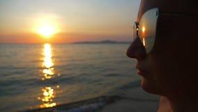 Por do sol ensolarado bonito no mar Vista através dos óculos de sol a mulher nos óculos de sol olha o por do sol no mar video estoque