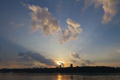 Por do sol esplêndido com nuvens atrás de uma arquitetura da cidade Imagens de Stock Royalty Free