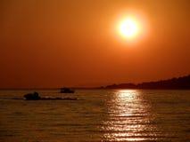 Por do sol, esqui do jato e barco Fotos de Stock