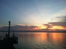 Por do sol fora da doca Imagens de Stock