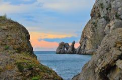 Por do sol glamoroso nas rochas grandes na costa rochosa do Mar Negro, Crimeia, Novy Svet Imagens de Stock