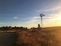 Por do sol gramíneo do campo do moinho de vento nenhum céu azul dos povos fotos de stock royalty free