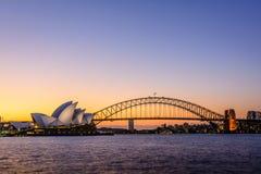 Por do sol icônico de Sydney Opera House e da ponte, Austrália Imagem de Stock Royalty Free
