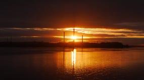 Por do sol industrial atrás do rio Foto de Stock Royalty Free