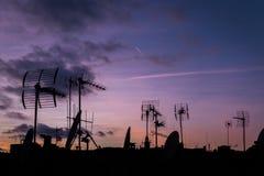 Por do sol lilás e muitas silhuetas dos telhados com antenas, Barcel Imagens de Stock Royalty Free