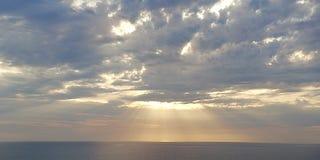 Por do sol do mar Os raios do sol de ajuste perfuram as nuvens Seascape Fundo fotos de stock royalty free