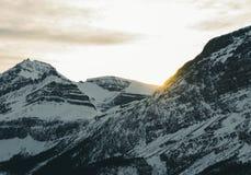 Por do sol morno temperamental acima das montanhas rochosas Fotografia de Stock