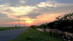 Por do sol na estrada do campo fotografia de stock royalty free