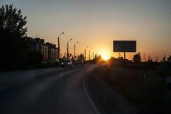 Por do sol na estrada de cidade com luzes no lado da estrada e de um quadro de avisos no verão imagem de stock royalty free