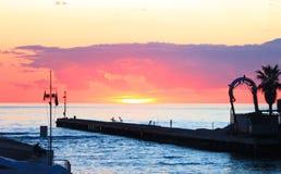 Por do sol na opinião do mar do porto porto pequeno imergido em cores alaranjadas e cor-de-rosa vívidas e brilhantes do por do so foto de stock royalty free