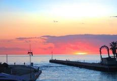 Por do sol na opinião do mar do porto porto pequeno imergido em cores alaranjadas e cor-de-rosa vívidas e brilhantes do por do so fotos de stock royalty free