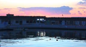 Por do sol na opinião do mar do porto porto pequeno imergido em cores alaranjadas e cor-de-rosa vívidas e brilhantes do por do so fotografia de stock