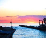 Por do sol na opinião do mar do porto porto pequeno imergido em cores alaranjadas e cor-de-rosa vívidas e brilhantes do por do so fotografia de stock royalty free