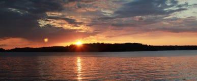 Por do sol na paisagem do horizonte do rio Por do sol vermelho sobre a opinião da água do lago Panorama escuro do rio do por do s imagem de stock