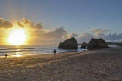 Por do sol na praia com as rochas no fundo Imagens de Stock