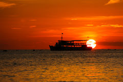 Por do sol na praia com barco de pesca imagem de stock