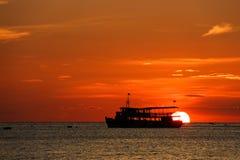 Por do sol na praia com barco de pesca imagens de stock royalty free