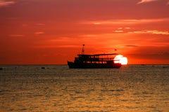 Por do sol na praia com barco de pesca foto de stock