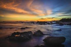 Por do sol na praia com ilhota da rocha Fotos de Stock