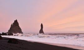 Por do sol na praia da areia do preto de Reynisfjara Fotografia de Stock
